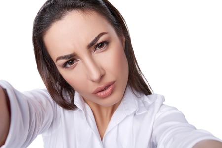 scepticism: Closeup of beautiful business woman making selfie photo on isolated white background with expression of confusion on her face