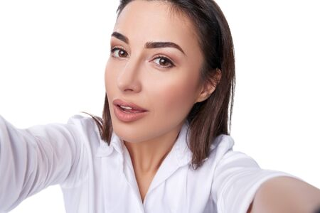 Closeup of beautiful playful business woman making selfie photo on isolated white background and looking at camera photo