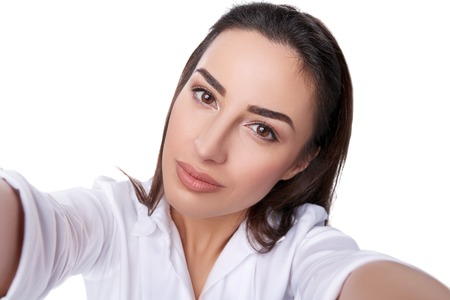 Closeup of beautiful business woman making selfie photo on isolated white background and looking at camera photo