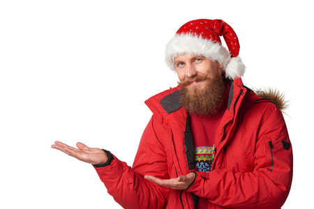 Bearded man in red winter jacket and christmas hat showing open hand palm with copy space for product or text, over white