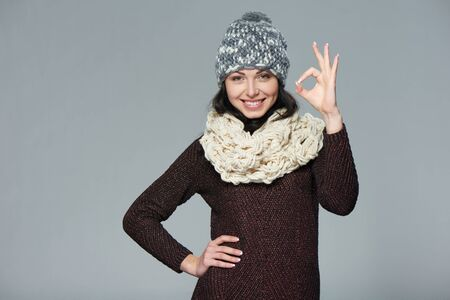 to muffle: Christmas girl, winter concept. Young beautiful smiling girl over grey background showing OK gesture Stock Photo