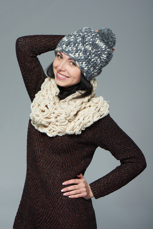 to muffle: Christmas girl, winter concept. Young beautiful smiling girl over grey background Stock Photo
