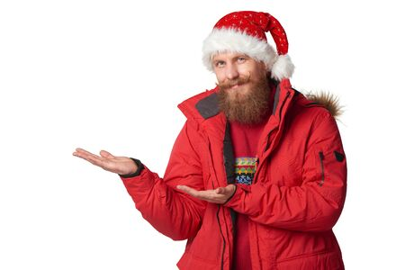 tog: Bearded man in red winter jacket and christmas hat showing open hand palm with copy space for product or text, over white