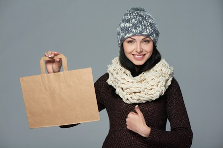 muffler: Winter holidays sale, shopping, Christmas concept. Portrait of smiling woman wearing warm winter hat and muffler showing shopping bag with empty copy space and gesturing thumb up