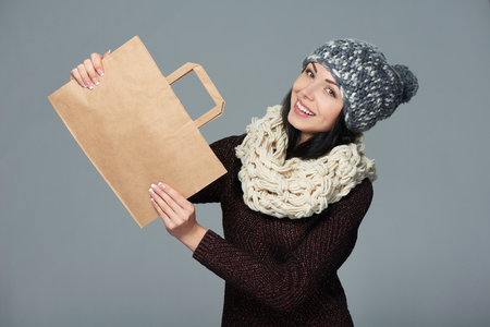 shopper: Winter holidays sale, shopping, Christmas concept. Portrait of smiling woman wearing warm winter hat and muffler showing shopping bag with empty copy space