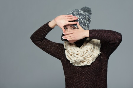 looking through frame: Pretty young woman in winter clothing making a frame with her hands, over grey background Stock Photo