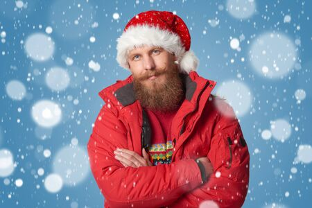 Bearded man in red winter jacket and Santa hat, over snow background Stock Photo