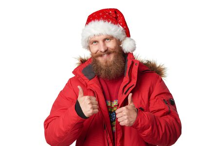Bearded man in red winter jacket and Santa hat giving double thumbs up, over white