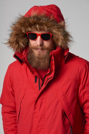 Portrait of a man wearing red winter Alaska jacket with fur hood and red sunglasses on, studio shot