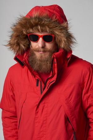 fur hood: Portrait of a man wearing red winter Alaska jacket with fur hood and red sunglasses on, studio shot