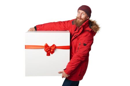 huge: Christmas, x-mas, winter gift concept. Man wearing red winter jacket carrying huge heavy gift box with red bow, isolated on white