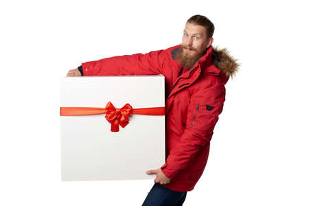 carry on: Christmas, x-mas, winter gift concept. Man wearing red winter jacket carrying huge heavy gift box with red bow, isolated on white