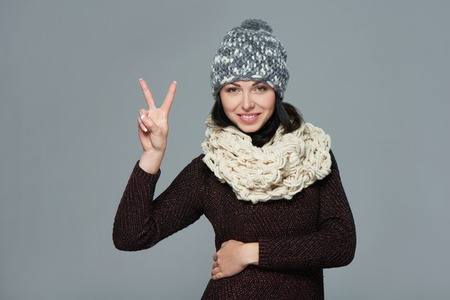 warm clothing: Happy beautiful woman wearing warm winter clothing showing a hand gesture peace sign, over grey background