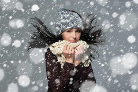 to muffle: Christmas girl, winter concept. Young beautiful smiling girl over snow background