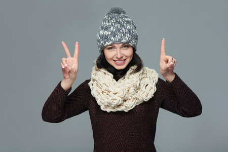 three fingers: Hand counting - three fingers. Portrait of woman on white background wearing woolen hat and sweater showing three fingers