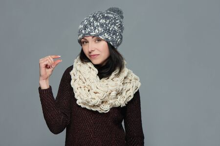Woman wearing warm winter clothing indicating little bit, over grey background Stock Photo