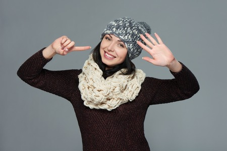 muffler: Hand counting - six fingers. Portrait of woman on grey background wearing woolen hat and muffler showing six fingers Stock Photo