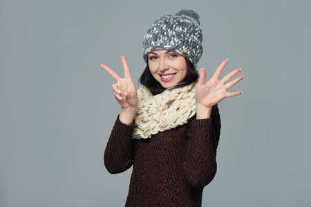 fingers: Hand counting - seven fingers. Portrait of woman on grey background wearing woolen hat and muffler showing seven fingers