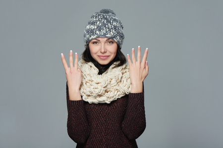 muffler: Hand counting - eight fingers. Portrait of woman on grey background wearing woolen hat and muffler showing eight fingers Stock Photo