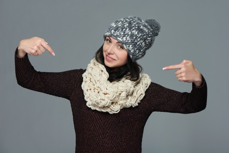 egocentric: Smiling woman wearing warm winter clothing pointing at herself, over grey background