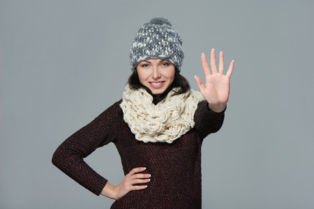five fingers: Hand counting - five fingers. Portrait of woman wearing woolen hat and muffler showing five fingers, giving high five gesture - success and winning concept.