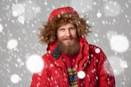 tog: Closeup portrait of bearded man in red winter jacket with hood on, over snow background