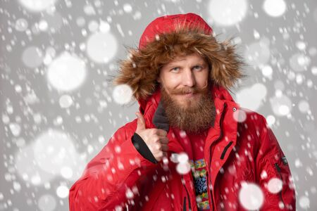 Closeup portrait of bearded man in red winter jacket with hood on showing thumb up gesture, over snow background