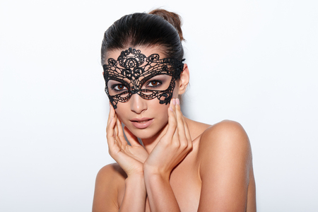 masquerade ball: Closeup portrait of beautiful woman with evening smokey makeup and black lace mask over her eyes Stock Photo