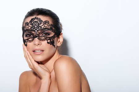 sexy glamour: Closeup portrait of beautiful woman with evening smokey makeup and black lace mask over her eyes Stock Photo