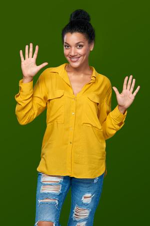 numero diez: Cuenta de la mano - diez dedos. Raza mixta afroamericana feliz - mujer caucásica que indica el número diez con sus dedos