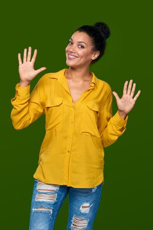 numero diez: Cuenta de la mano - diez dedos. Feliz raza mixta afroamericana lúdico - mujer caucásica que indica el número diez con sus dedos