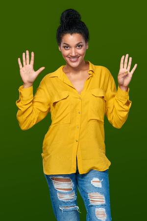 numero nueve: Cuenta de la mano - nueve dedos. Raza mixta afroamericana feliz - mujer caucásica que indica el número nueve con sus dedos