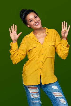 numero nueve: Cuenta de la mano - nueve dedos. Feliz raza mixta lúdico afroamericano - mujer caucásica que indica el número nueve con sus dedos