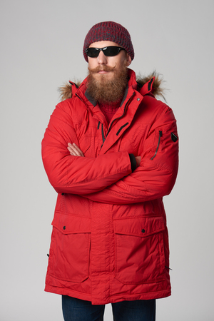 Portrait of a serious bearded man wearing red winter Alaska jacket and sunglasses standing with folded hands and looking at camera, studio shot Stock Photo