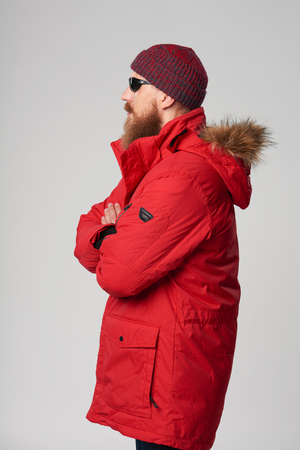 Side view of a serious bearded man wearing red winter Alaska jacket and sunglasses standing with folded hands and looking forward, studio shot