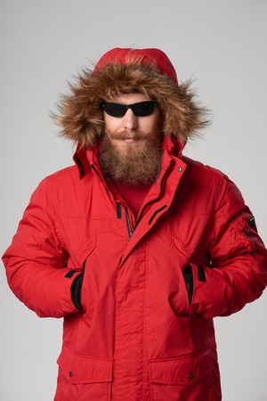 tog: Portrait of a serious bearded man wearing red winter Alaska jacket and sunglasses standing with hands in pockets and the hood on,  looking at camera, studio shot
