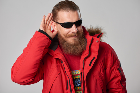 fur hood: Portrait of a man wearing red winter Alaska jacket  with fur hood on,  looking forward out of frame, studio shot Stock Photo