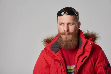 tog: Closeup portrait of bearded man in red winter jacket  over grey background