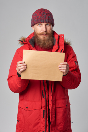 Portrait of a man wearing red winter Alaska jacket showing big envelope - banner with copy space for text, looking at camera Stock Photo
