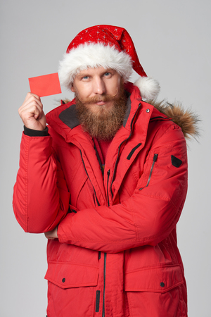 Bearded man in red winter jacket and christmas hat showing blank credit card with blank copy space, over grey background Stock Photo