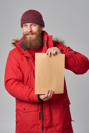 Portrait of a smiling man wearing red winter Alaska jacket showing big envelope - banner with copy space for text, looking at camera Stock Photo