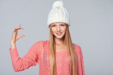 product: Portrait of woman wearing warm winter clothing holding imaginary product in her fingers, over gray background Stock Photo