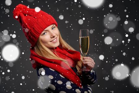 personas festejando: Christmas, New Year, winter holidays celebration concept. Young beautiful smiling girl wearing winter hat and scarf holding glass of champagne over snow background Foto de archivo