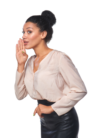 blab: Surprised mixed race caucasian - african american business woman whispering gossip, over white background Stock Photo