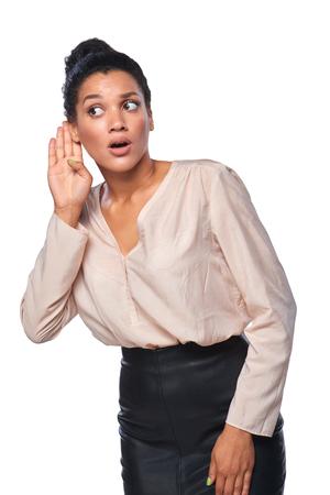 oido: Mujer de negocios que escucha el chisme con la atención con la mano en la oreja, sobre fondo blanco Foto de archivo