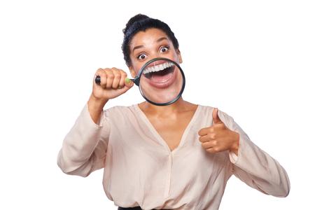la boca: Mujer divertida que sonríe y que muestra los dientes a través de una lupa, haciendo un gesto pulgar hacia arriba, sobre el fondo blanco Foto de archivo