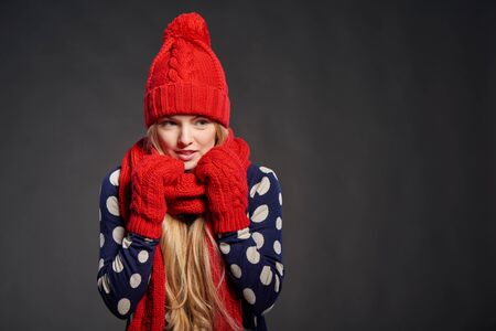 knit: Young beautiful woman muffling in warm knitted scarf for warmth, over grey background Stock Photo