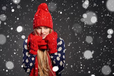 warmth: Christmas girl, winter concept. Young beautiful woman muffling in warm knitted scarf for warmth, over snow background Stock Photo