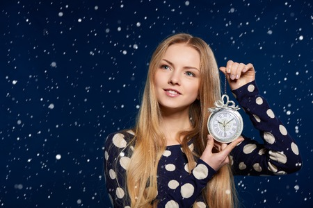 thoughts: Christmas, New Year, winter holidays celebration concept. Dreaming woman holding a clock over snow background, looking in thoughts up at blank copy space