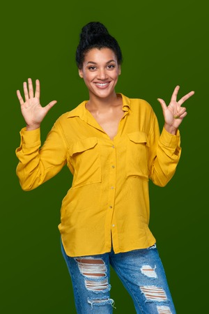 number eight: Hand counting - eight fingers. Happy mixed race african american - caucasian woman indicating the number eight with her fingers Stock Photo